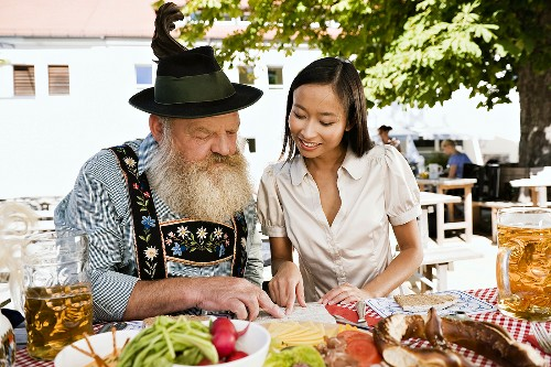 Asian woman and man in Bavarian dress in beer garden