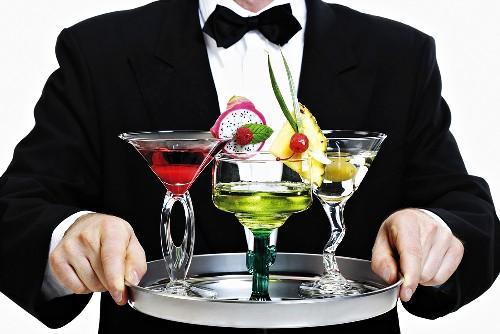 Bartender serving tray of different cocktails