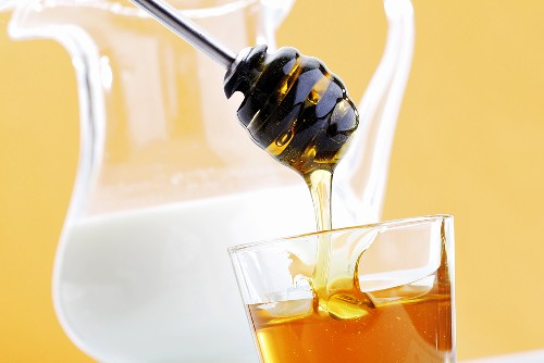 Honig tropft vom Honiglöffel in Glas, Milchkrug