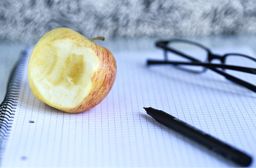 Half eaten apple and spectacles on notepad