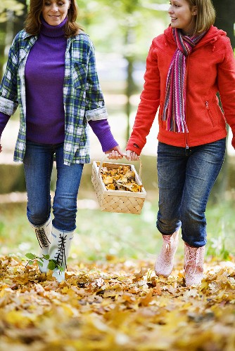 Mother and daughter carrying basket of chanterelles