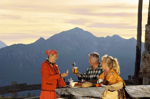 Peasant woman serving couple at alpine hut