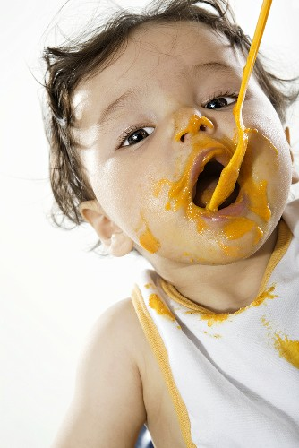 Baby (6-9 months) eating from spoon, portrait