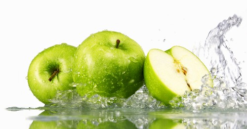 Green apples, whole and halved, with splashing water