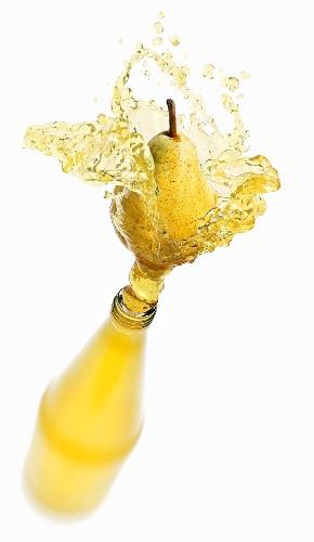 Pear juice splashing out of bottle
