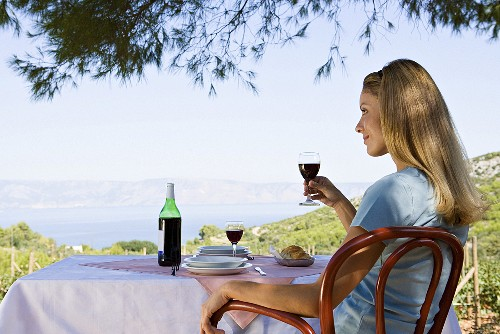 A woman sitting at a table with a glass of wine looking out to sea