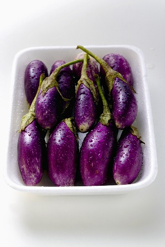 Baby aubergines with drops of water in white dish