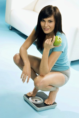 Young woman with apple in hand squatting on scales