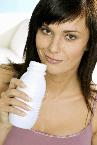 Young woman with a bottle of drinking yoghurt