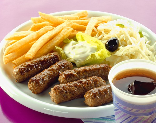 Cevapcici with chips, tzatziki and cabbage salad