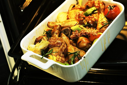 Oven-baked chicken thighs with vegetables and rosemary