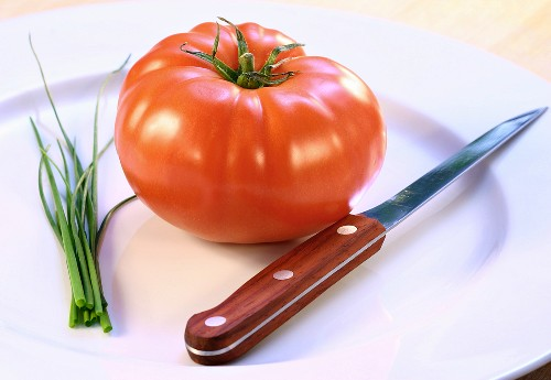 A tomato, chives and a knife on a plate