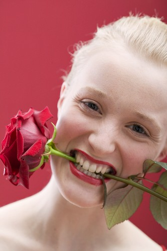 Young woman with a red rose in her mouth