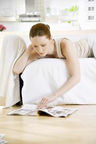 Young woman lying on sofa reading newspaper