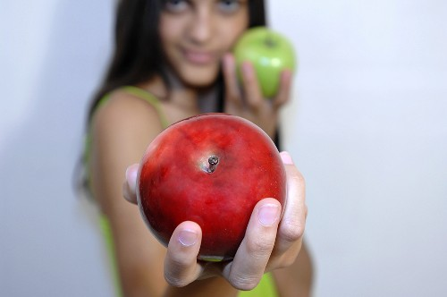 Young woman holding one red and one green apple
