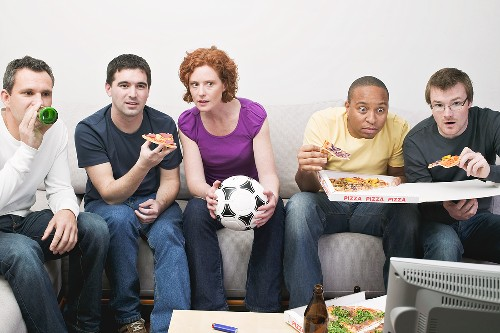 Friends with football, pizza & beer sitting in front of TV