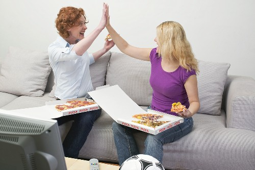 Two friends eating pizza and cheering in front of TV