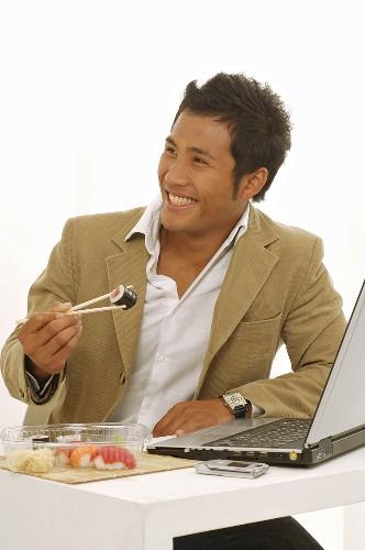 Asian man eating sushi while sitting at laptop