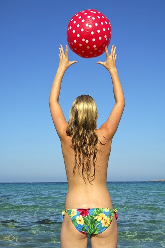 Woman playing with a beach ball in the sea