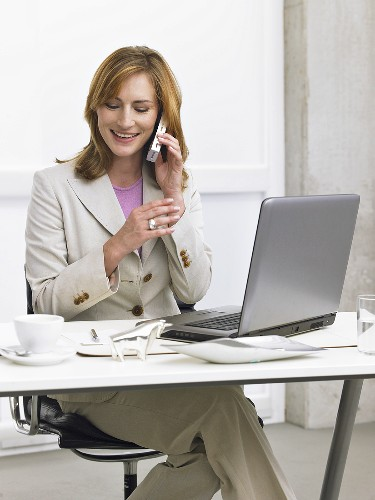 Businesswoman sitting at her desk making a phone call