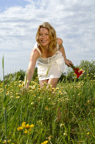 Young woman picking a bunch of summer flowers in a meadow