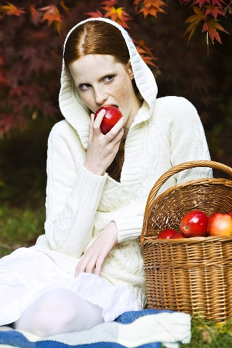 Young woman eating apple in park in autumn