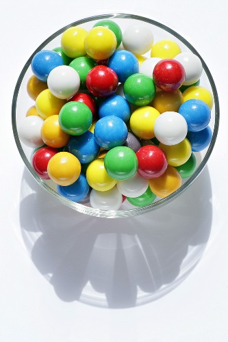 Lots of coloured chewing gum balls in a glass bowl