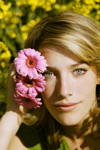 Young woman putting pink gerberas behind her ear