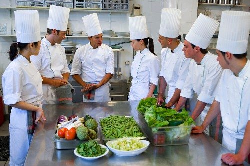 Trainee chefs learning to cook from a head chef in a commercial kitchen