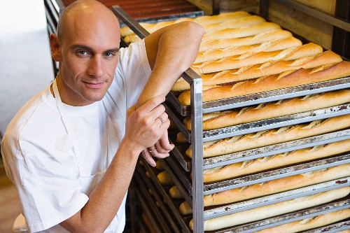 Baker with trays of baguettes in bakery