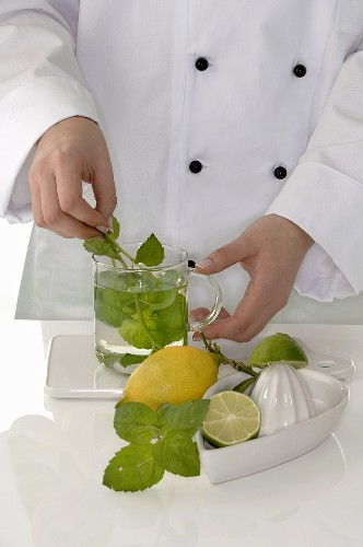 Female chef making peppermint tea with lemon