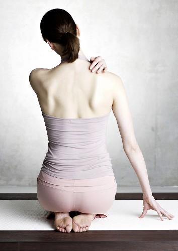 Woman kneeling on yoga mat (back view)