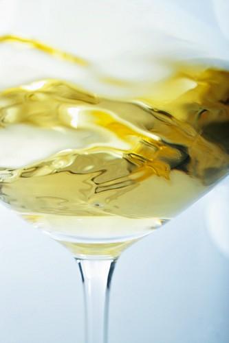 A glass of white wine being swirled