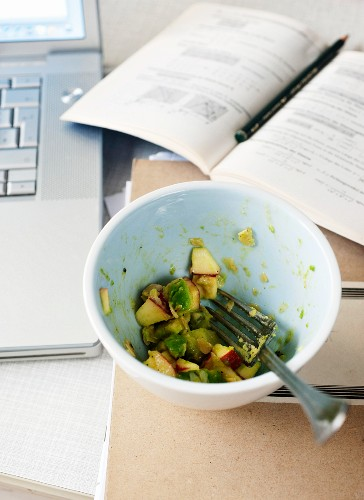 Half eaten avocado salad with apples next to a laptop and book