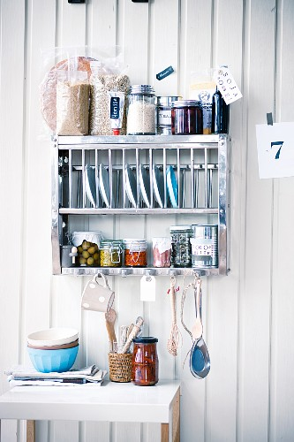 Plates, spices and other supplies on a kitchen shelf