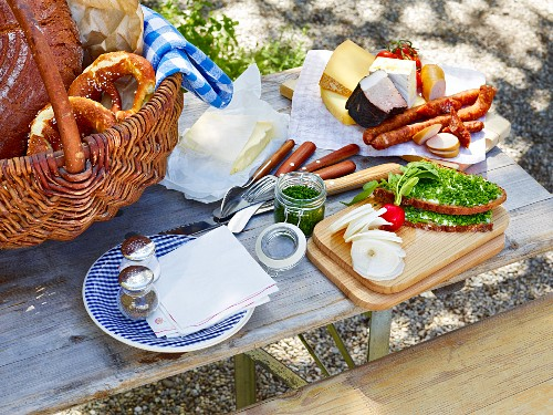 Supper served from a table outside featuring bread, pretzels, cheese and cold meats