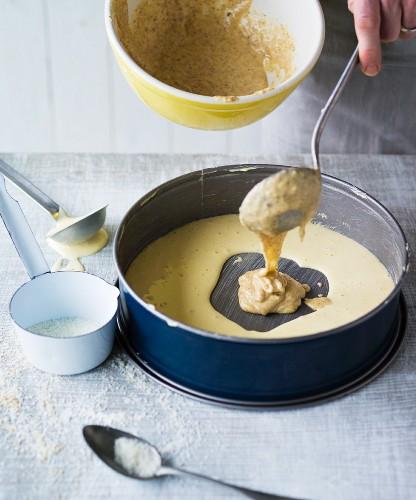 Mandarin marble cake being made – nut cake mix being added to the baking tin