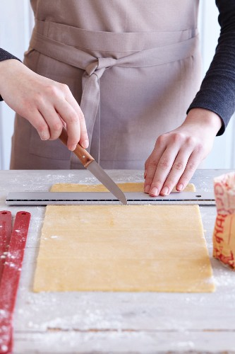 Zebra biscuits being made: rolled out pastry being cut into strips