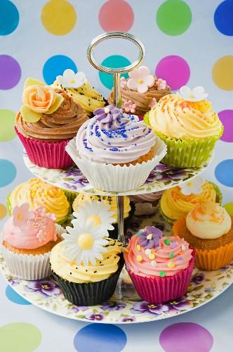 Mehrere Cupcakes mit Zuckerblumen auf einer Etagere