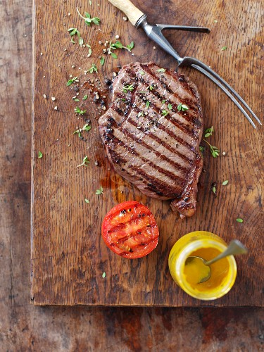 Grilled steak with grilled tomatoes and mustard