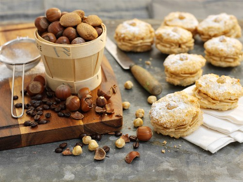 Coffee and hazelnut whoopie pies with icing sugar, nuts and coffee beans