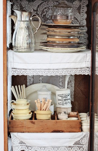 Stacked plates next to thermos jugs, china crockery with vintage-style cutlery and lace doilies in open display cabinet