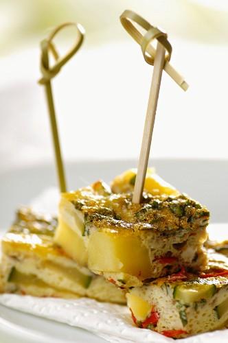 Spanish tortilla; made of eggs, potatoes, zucchini, garlic, chillies and fresh mint - cut and put on sticks
