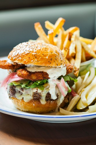 Cheeseburger Topped with Fried Oysters and Mayo Sauce; Served with Pickle and French Fries