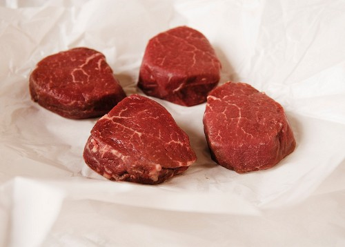 Four Raw Filet Mignon Steaks on Butcher's Paper