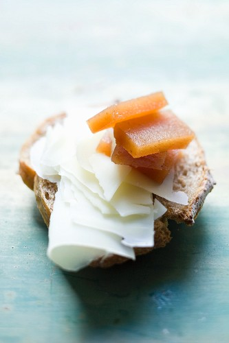 Bread topped with wafer-thin slices of cheese, with quince jelly