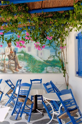 Chairs and tables in corner of terrace in front of mural with bucolic motif below climber-covered pergola
