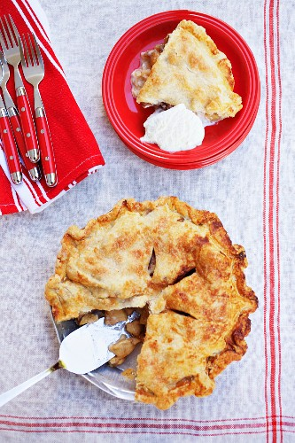 A Slice of Apple Pie with a Scoop of Vanilla Ice Cream on a Red Plate; Remainder of Pie in Baking Dish