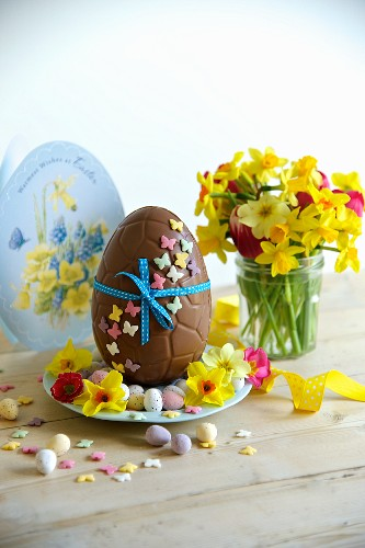 Chocolate Easter egg, sugar eggs and a small bunch of narcissi