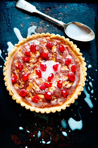 A Bakewell tart with glacé cherries, slivered almonds and sugar icing